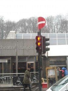 Doi omuleți roșii la semafor și semnul interzis îndoit