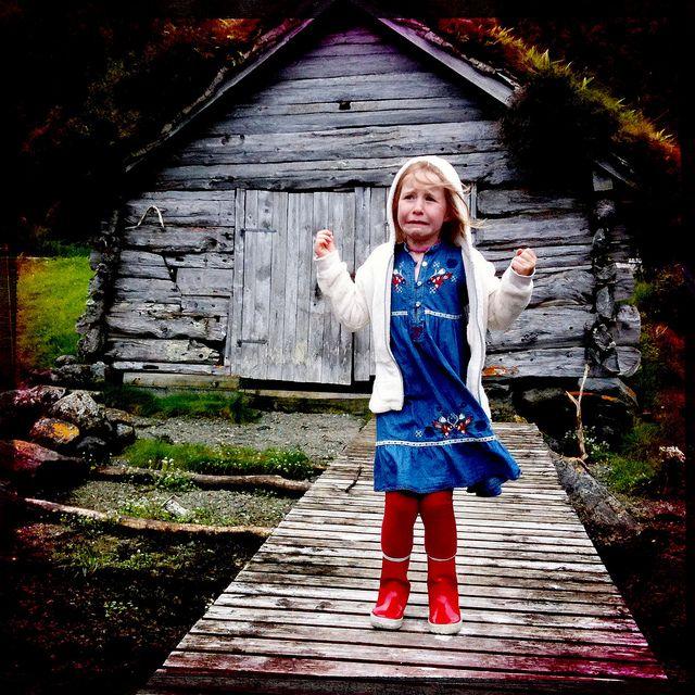 Un copil din Norvegia în fața unei cabane tipice acestei țări: poate îi e frig sau poate doar vrea acasă (foto: Gunnvor Karita)